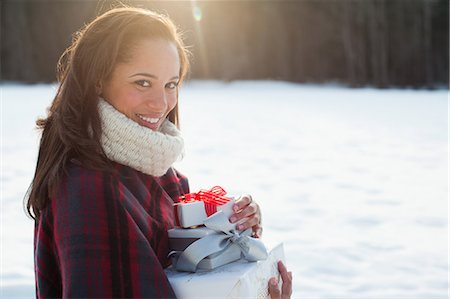 Portrait of smiling woman holding Christmas gifts in snow Stock Photo - Premium Royalty-Free, Code: 635-07364073