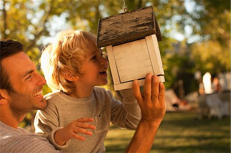 Father and son examining birdhouse Stock Photo - Premium Royalty-Free, Code: 635-07364200