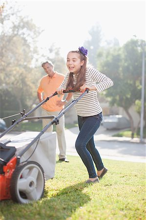 Father and daughter mowing lawn together Stock Photo - Premium Royalty-Free, Code: 635-07364232