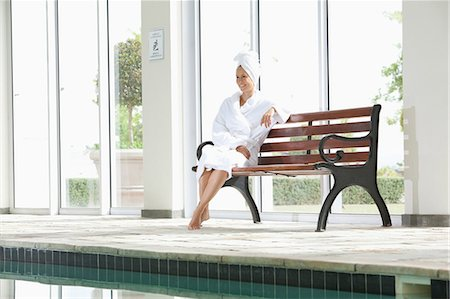 self indulgence - Portrait of smiling woman in bathrobe sitting on bench poolside at spa Stock Photo - Premium Royalty-Free, Code: 635-07364325