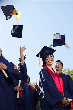 Graduates throwing caps in air outdoors Stock Photo - Premium Royalty-Free, Code: 635-07364427