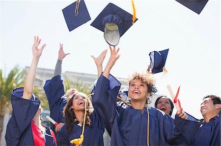 Graduates tossing caps into the air Stock Photo - Premium Royalty-Free, Code: 635-07364551