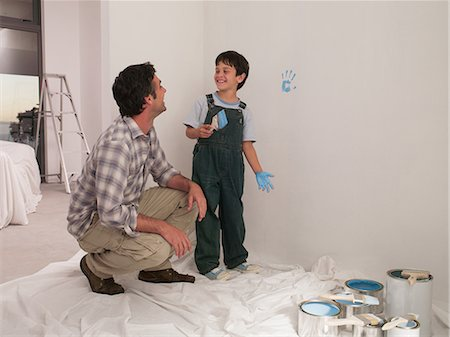 Father watching son make handprint on wall with paint Stock Photo - Premium Royalty-Free, Code: 635-07365261