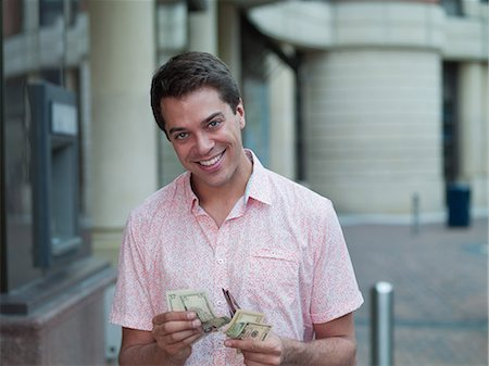 showing - Smiling man counting money near ATM machine Stock Photo - Premium Royalty-Free, Code: 635-07365297