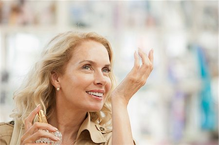 smelling - Smiling woman testing perfume in store Stock Photo - Premium Royalty-Free, Code: 635-07365311