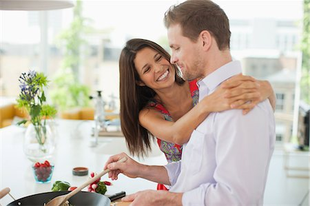 Woman hugging husband while he's cooking in kitchen Stock Photo - Premium Royalty-Free, Code: 635-07365352