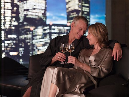 Couple in bathrobes drinking wine in living room at night Stock Photo - Premium Royalty-Free, Code: 635-07365388
