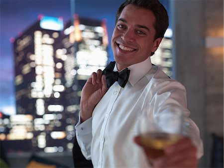 self indulgence - Man in tuxedo drinking cocktail with cityscape in background Stock Photo - Premium Royalty-Free, Code: 635-07365381