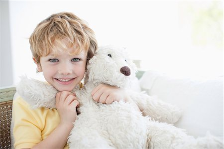 Smiling boy hugging teddy bear Stock Photo - Premium Royalty-Free, Code: 635-07365397