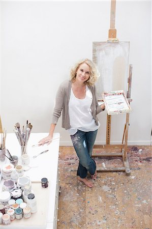 Woman holding paintbrush and palette in art studio Stock Photo - Premium Royalty-Free, Code: 635-07365506
