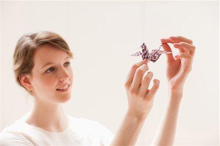 paper - Smiling woman holding origami bird Stock Photo - Premium Royalty-Free, Code: 635-07456943