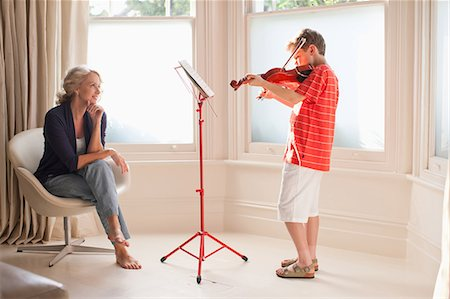 Smiling woman watching boy play violin Stock Photo - Premium Royalty-Free, Code: 635-07456953