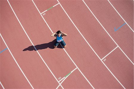 filipino (male) - Disappointed runner kneeling on track Stock Photo - Premium Royalty-Free, Code: 635-07521975