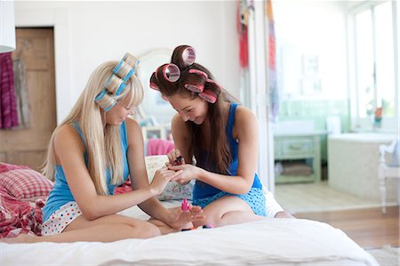 Women painting fingernails with curlers in hair Stock Photo - Premium Royalty-Free, Code: 635-07521994