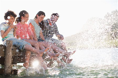 Family on dock splashing feet in lake Stock Photo - Premium Royalty-Free, Code: 635-07522051