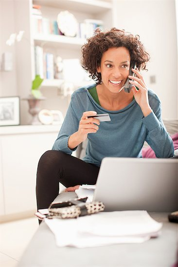 Woman making online purchase and talking on cellphone Stock Photo - Premium Royalty-Free, Image code: 635-07595755