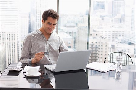Businessman shopping online with credit card Stock Photo - Premium Royalty-Free, Code: 635-07595938