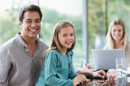 Father watching daughter count coins Stock Photo - Premium Royalty-Free, Code: 635-07595940