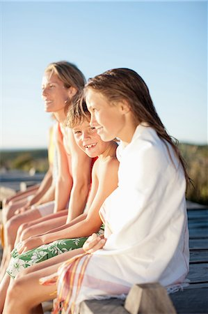 preteen girl topless - Family sitting on pier near beach Stock Photo - Premium Royalty-Free, Code: 635-07670855