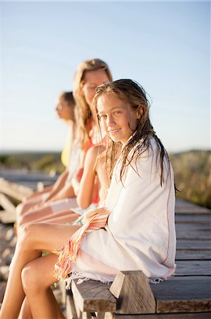 preteen girl wet clothes - Family sitting on pier near beach Stock Photo - Premium Royalty-Free, Code: 635-07670856