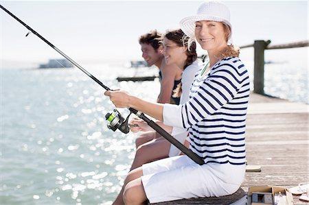 Friends fishing off pier at ocean Stock Photo - Premium Royalty-Free, Code: 635-07670939