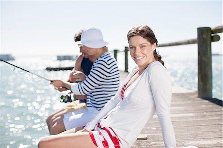 Friends fishing off pier at ocean Stock Photo - Premium Royalty-Free, Code: 635-07670940