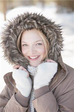 fur - Portrait of smiling woman wearing fur hood coat Stock Photo - Premium Royalty-Free, Code: 635-07762757