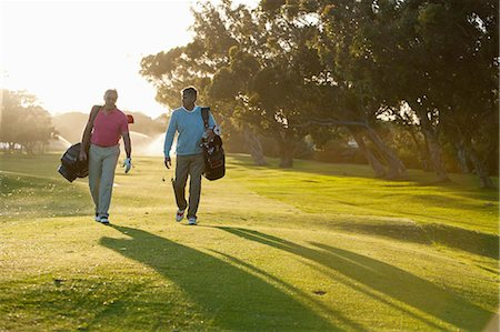 Men carrying golf bags on golf course Stock Photo - Premium Royalty-Free, Code: 635-07762869
