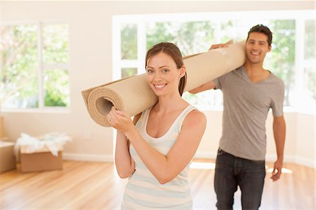 Couple carrying carpet into new house Stock Photo - Premium Royalty-Free, Code: 635-07763021