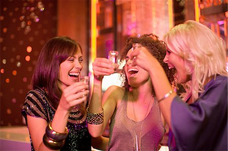 Friends toasting shot glasses in nightclub Stock Photo - Premium Royalty-Free, Code: 635-07763049