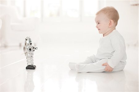 Baby on floor looking at toy robot Stock Photo - Premium Royalty-Free, Code: 635-07763070
