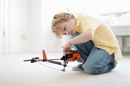 fly - Boy playing with toy helicopter Stock Photo - Premium Royalty-Free, Code: 635-08172969