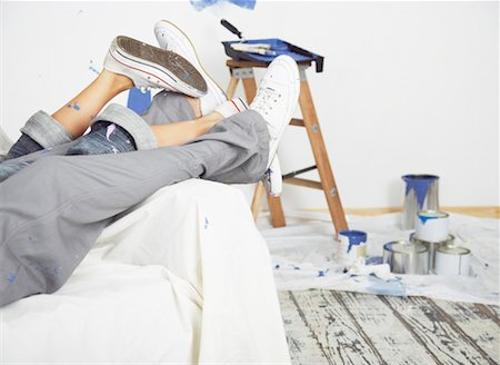 Man and woman waist down on sofa with paint Stock Photo - Premium Royalty-Free, Code: 635-01346518