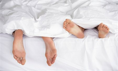 Male and female feet in bed under blankets Stock Photo - Premium Royalty-Free, Code: 635-01346862