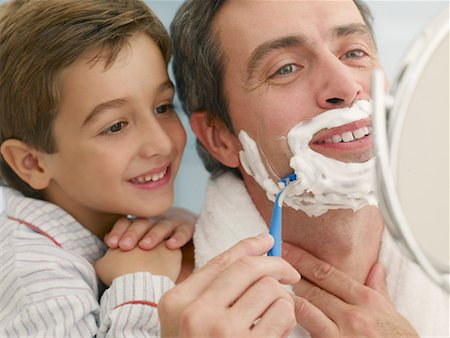 Young boy watching his father shaving in a mirror Stock Photo - Premium Royalty-Free, Code: 635-01347073