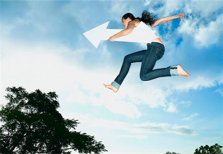 Woman with blank arrow leaping outdoors Stock Photo - Premium Royalty-Free, Code: 635-01347428