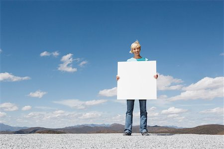 Woman with blank sign outdoors Stock Photo - Premium Royalty-Free, Code: 635-01347439