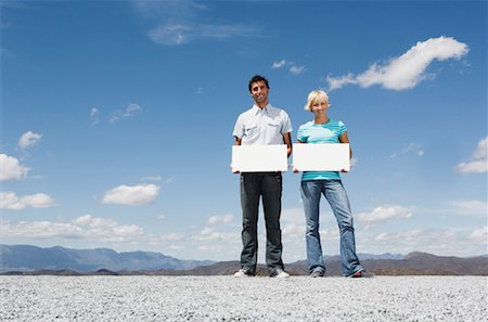 Man and woman outdoors with blank signs Stock Photo - Premium Royalty-Free, Code: 635-01347503