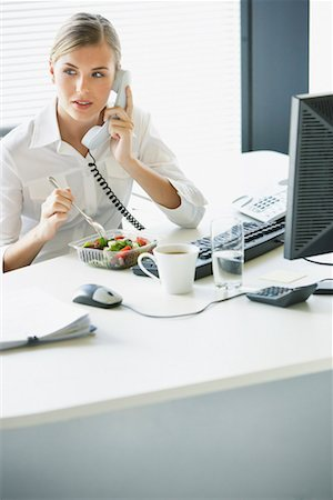 Businesswoman eating salad and talking on telephone at desk Stock Photo - Premium Royalty-Free, Code: 635-01347517