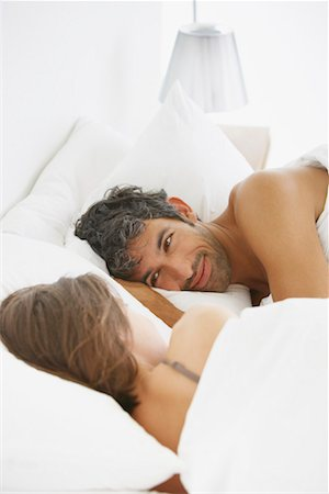 Woman and man lying down in bed Stock Photo - Premium Royalty-Free, Code: 635-01347595