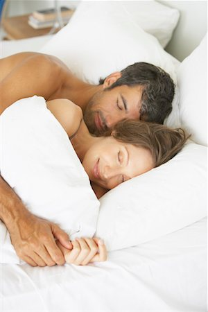 Woman and man lying down in bed Stock Photo - Premium Royalty-Free, Code: 635-01347633