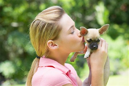 dog kissing girl - Girl kissing puppy dog Stock Photo - Premium Royalty-Free, Code: 635-01347756