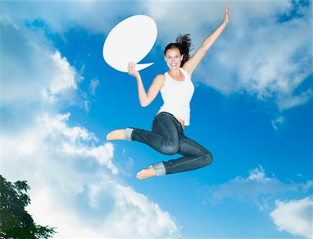 Woman with speech balloon leaping outdoors with blue sky and clouds Stock Photo - Premium Royalty-Free, Code: 635-01347912