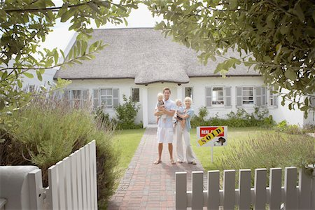 sold sign - Man and woman holding babies in front of house with sold sign and white fence Stock Photo - Premium Royalty-Free, Code: 635-01348155