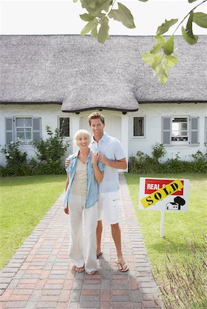 sold sign - Man and woman outdoors in front of house with sold sign Stock Photo - Premium Royalty-Free, Code: 635-01348275