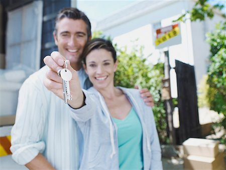 sold sign - Man and woman with keys outdoors with moving van and sold sign on house smiling Stock Photo - Premium Royalty-Free, Code: 635-01348293