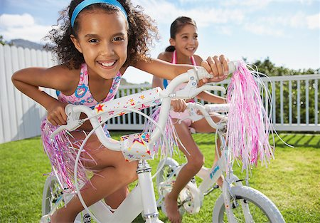 Two girls riding bicycles outdoors smiling Stock Photo - Premium Royalty-Free, Code: 635-01488981
