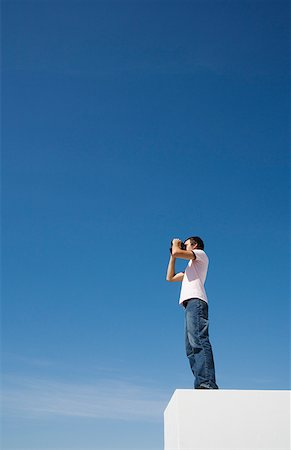 Man on pedestal with binoculars and blue sky outdoors Stock Photo - Premium Royalty-Free, Code: 635-01489075
