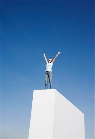 Woman standing on wall outdoors with arms up Stock Photo - Premium Royalty-Free, Code: 635-01489187
