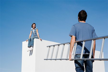Woman sitting on wall and man with ladder outdoors Stock Photo - Premium Royalty-Free, Code: 635-01489183